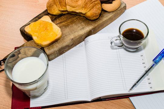 Agenda, quaderno, penna e colazione. Esprime concetti legati al lavoro