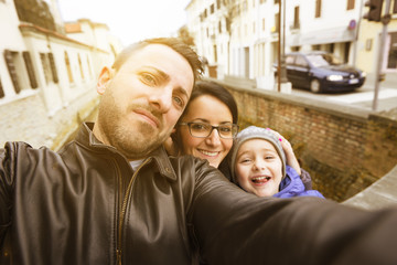 selfie of a happy family on a walk in town with autumnal atmosphere