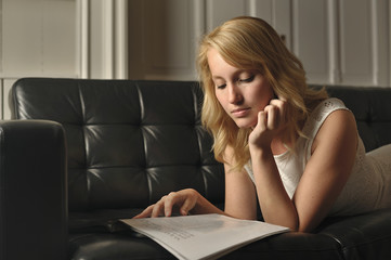 Blonde woman lying on the couch reading