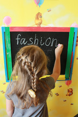 girl with nice plaits writes Fashion on blackboard