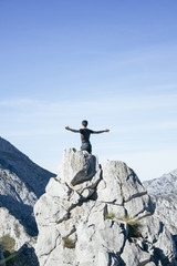 Man with arms extended on the top of a mountain