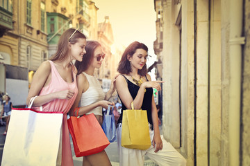 Girls looking at the window of a shop