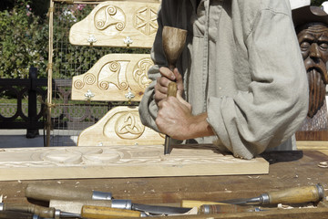 forefront of hands of a wood sculptor carving wood