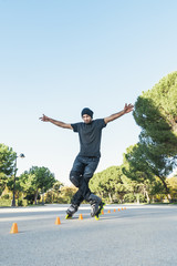 Urban young man on roller skates on the road at summer time