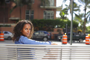 Woman sitting on a bus bench looking over shoulder