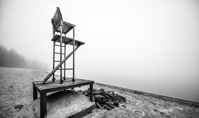Empty beach lifeguard chair - black&white - lonely lifeguard seat stands empty on fog shrouded November beach in Ontario Canada.