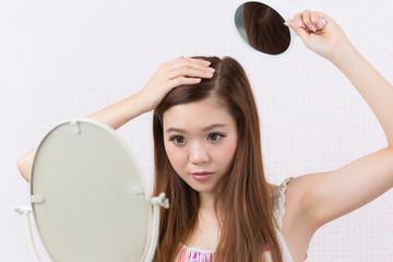 鏡で頭頂部をチェックする女性
