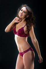 Young slim brunette girl posing in a studio in lacy underwear