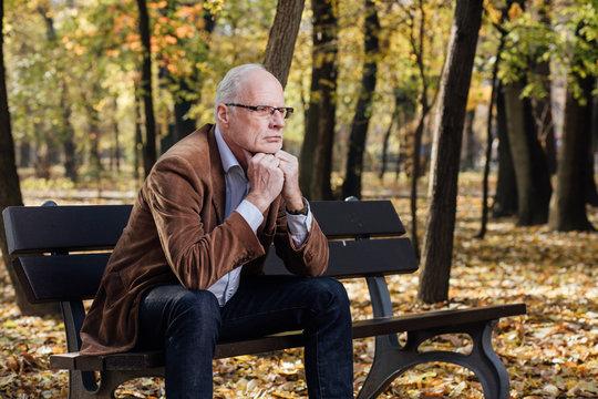 old elegant man sitting on bench outside