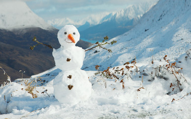 Happy snowman in mountains.