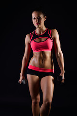Portrait of young fitness woman posing with dumb-bells. Muscular