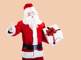 Santa Claus with gift posing on color background