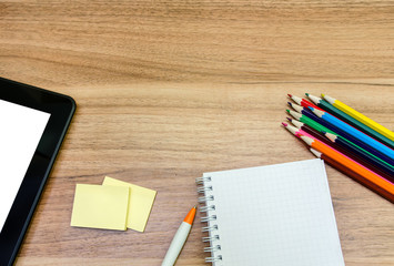 Blank paper and colorful pencils on the wooden table
