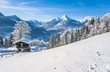 Idyllic winter landscape in the Alps with traditional mountain chalet