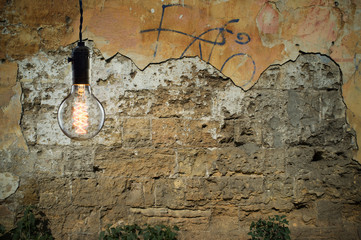 Idea concept - Vintage incandescent bulb on wall background