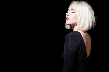 Blonde in a black dress with an open back on a black background