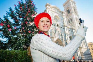 Traveler woman taking photo in Christmas decorated Florence