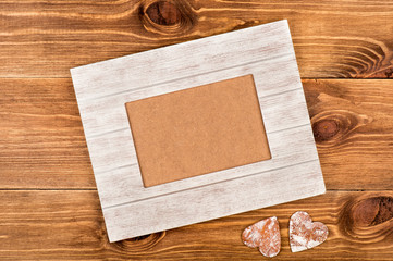 White wooden frame for picture on the wooden background.