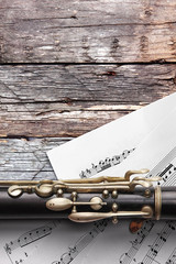 Old flute with sheet music on rusty wooden boards