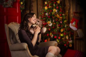 Woman with teddy bear near christmas decorations