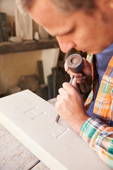 Fototapete - Stone Mason At Work On Carving In Studio