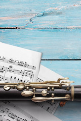 Old flute with sheet music on blue wooden boards