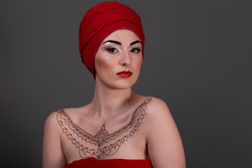 Middle eastern beauty in a scarf red lips isolated gray backgrou