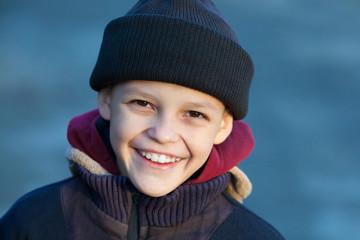 portrait of a little happy homeless boy