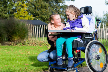 Disabled girl relaxing outside / disabled girl relaxing outside together with a care assistant
