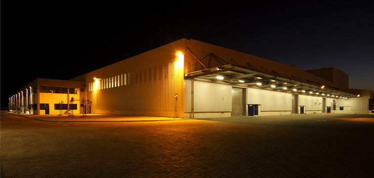 External wide angle view of modern warehouse at night