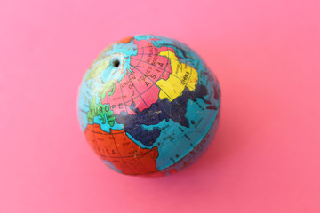 Close up of world globe - top view - travel destination and love different cultures concept - place for text - on pink background