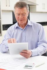 Senior Man Using Digital Tablet To Check Personal Finances