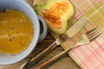 Pumpkin yellow soup in blue dish, slice of pumpkin on plaid table cloth, spoon and fork