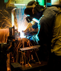 MIG welder uses torch to make sparks during manufacture of metal equipment.