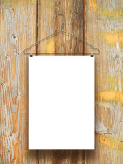Single hanged paper sheet with hanger on stained and weathered wooden board background