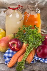 .Different bottles of juice with ripe fruits and vegetables on rustic table and in front of the linen background..
