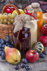 Different bottles of fresh juice with ripe fruits and vegetables on rustic table and in front of wood.
