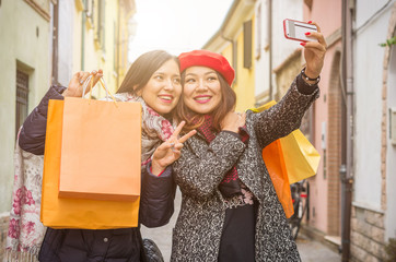 """Beautiful girls with shopping bags taking a """"selfie"""" with their cell phone"""
