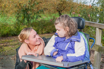 A disabled child in a wheelchair relaxing outside together with help from a voluntary care worker