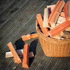 chopped firewood stack at the basket at the wooden floor