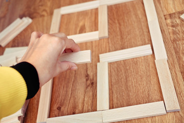 The hand establishes a wooden  construction plan for house.