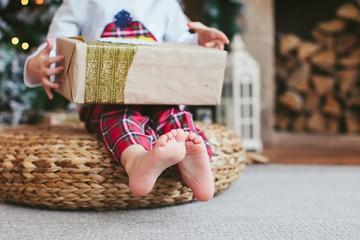 a little boy holding a Christmas box
