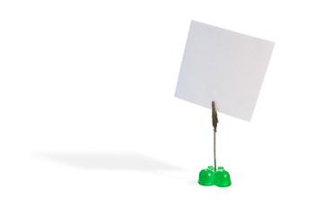 Grüner Zettelhalter mit leerem Notizzettel auf weißem Hintergrund