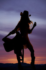 silhouette of a cowgirl in a skirt holding a saddle
