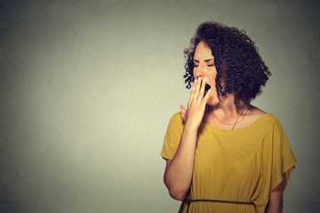 sleepy young woman with wide open mouth yawning eyes closed looking bored Wall mural