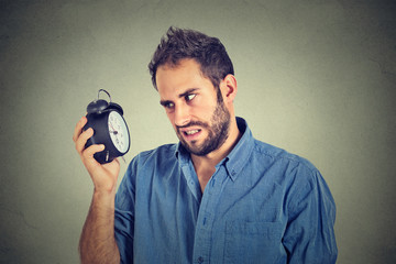 Stressed annoyed man with alarm clock. It is too early for that meeting