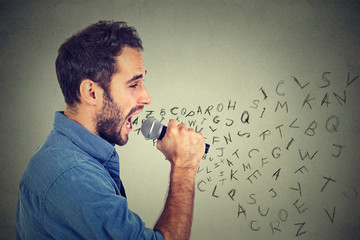 Young man singing in microphone with alphabet letters coming out of his mouth