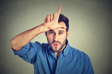 young man showing loser sign on forehead, looking at you with disgust