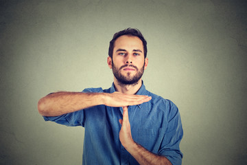 Young man giving showing time out hands gesture