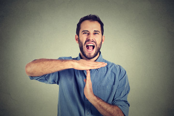 Young man showing time out hand gesture, frustrated screaming to stop